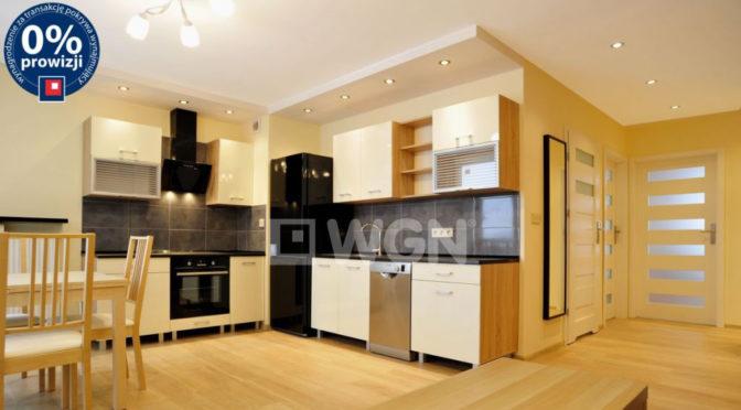 widok z salonu na nowoczesny aneks kuchenny w ekskluzywnym apartamencie do wynajmu w Katowicach