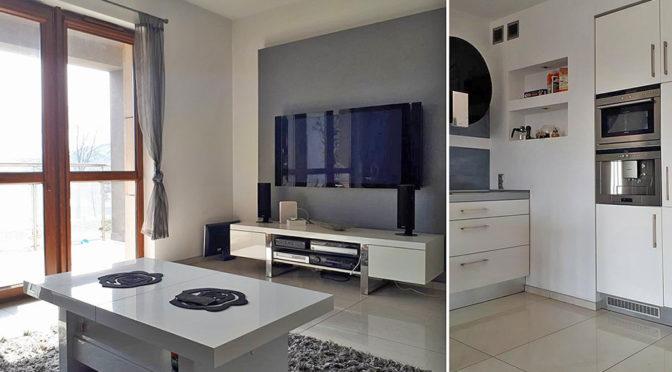 po lewej ekskluzywny salon, po prawej nowoczesna kuchnia w luksusowym apartamencie do wynajmu w Krakowie