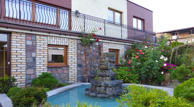 widok od strony ogrodu i fontanny na ekskluzywną rezydencję do sprzedaży