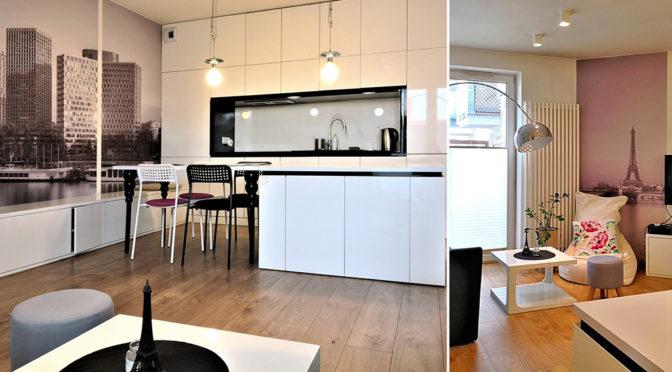 po lewej nowoczesny aneks kuchenny, po prawej salon w stylu klasycznym w ekskluzywnym apartamencie do wynajmu w Krakowie