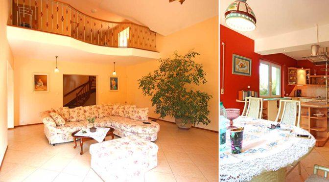 po lewej przestronny salon z antresolą, po prawej umeblowana stylowo kuchnia w ekskluzywnej rezydencji do wynajmu w Szczecinie