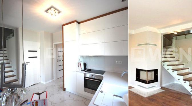 nowocześnie urządzona kuchnia oraz kominek w salonie ekskluzywnej rezydencji do wynajmu Szczecin (okolice)