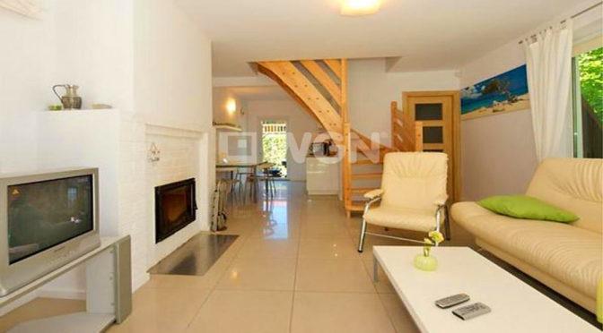 komfortowy salon z kominkiem w ekskluzywnej rezydencji do sprzedaży nad morzem