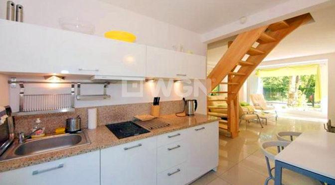 widok na kuchnię i schody na drugi poziom w ekskluzywnej rezydencji do sprzedaży nad morzem