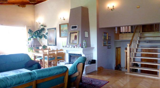 kameralny salon z kominkiem w luksusowej rezydencji na sprzedaż Mazury