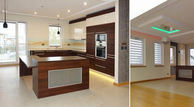 po lewej nowoczesna kuchnia z wyspą, po prawej salon w ekskluzywnym apartamencie na sprzedaż Brodnica