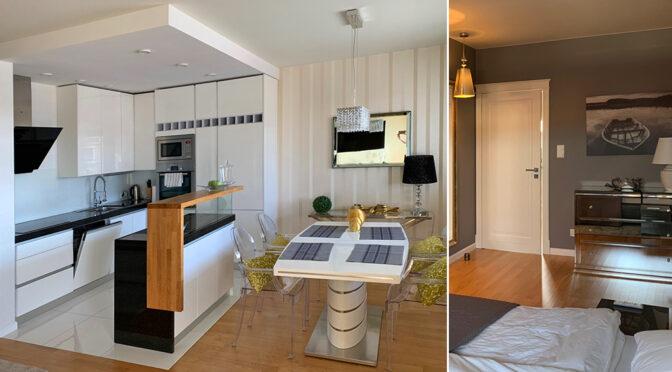 po lewej nowoczesny aneks kuchenny z jadalnią, po prawej fragment salonu w ekskluzywnym apartamencie na wynajem Mazury
