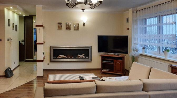 elegancki pokój dzienny z kominkiem w ekskluzywnym apartamencie do sprzedaży Nowogard