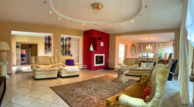 kameralny pokój dzienny z okazałym kominkiem w luksusowej rezydencji do sprzedaży Konin (okolice)