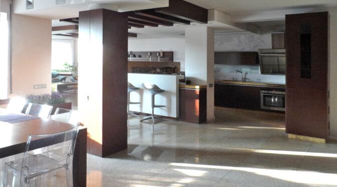 widok z salonu na nowoczesną zabudowę kuchni w ekskluzywnej rezydencji do sprzedaży Piotrków Trybunalski