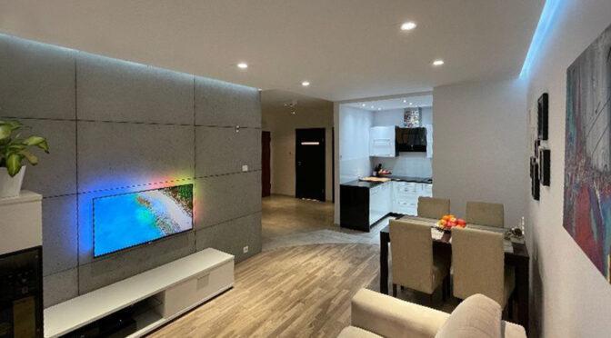 zaprojektowane zgodnie z najnowszymi trendami wnętrze pokoju gościnnego w luksusowym apartamencie na sprzedaż Pruszcz Gdański