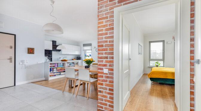 po lewej salon z aneksem kuchenny, po prawej sypialnia w ekskluzywnym apartamencie na sprzedaż Szczecin
