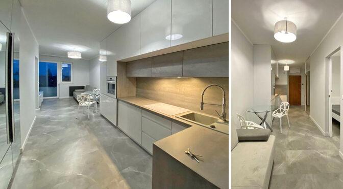 po lewej nowoczesna kuchnia, po prawej salon w luksusowym apartamencie do sprzedaży Szczecin