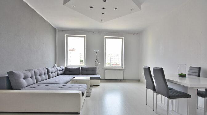 zaaranżowany w klasycznej bieli salon w ekskluzywnym apartamencie na sprzedaż Elbląg
